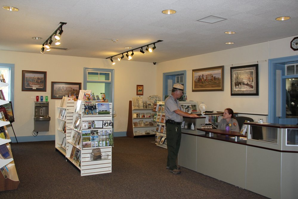 Two park rangers converse at the Visitor Center Information Desk.