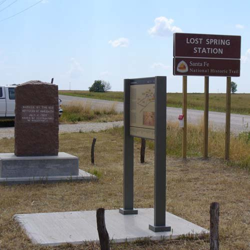 Brown metal site sign, red stone DAR marker, and tall interpretive panel. located near the main road and parking area.