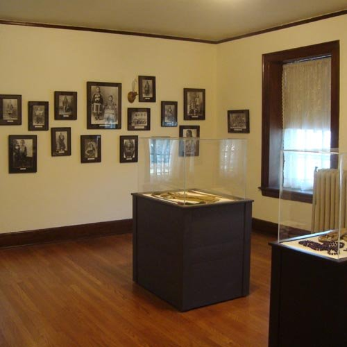 An open room with several photos of Kaw boys on the wall and two displays of artifacts.
