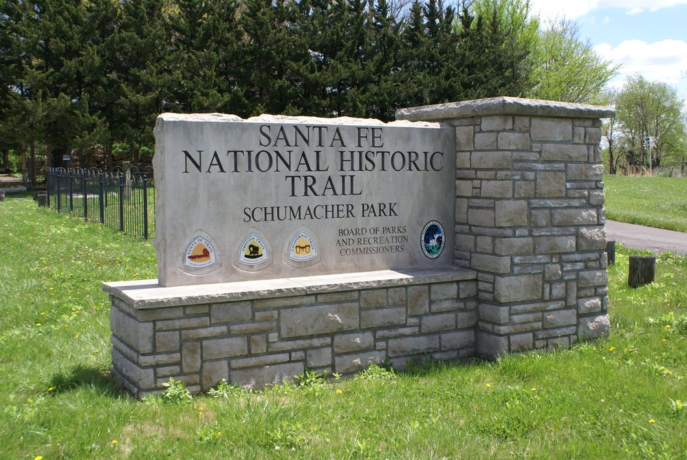 Large, engraved stone sign for Shumacher Park that includes several National Historic Trail logos.