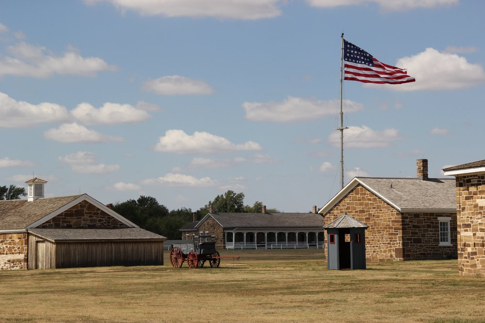 Image of fort's sandstone buildings with a U.S. flag flying from the flag pole.